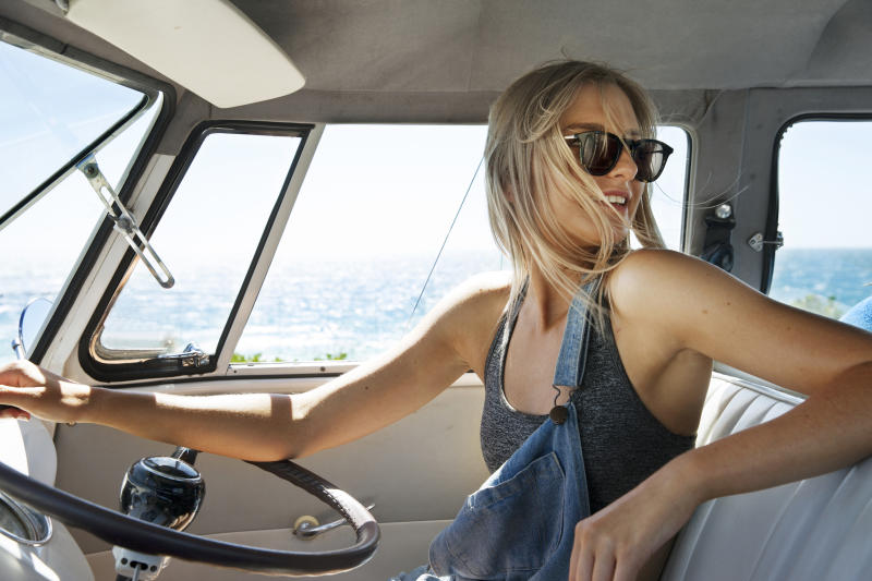 A woman drives a van with the beach in the background.