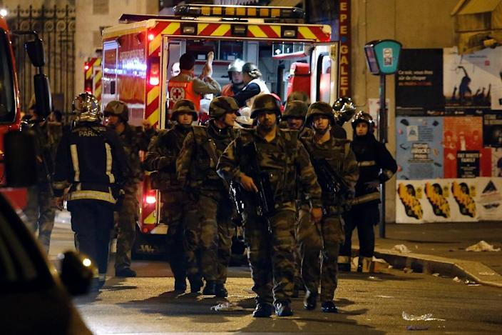 Soldiers walk in front of an ambulance as rescue workers evacuate victims near La Belle Equipe, Rue de Charonne, on November 14, 2015 after a series of gun attacks across Paris (AFP Photo/Pierre Constant)