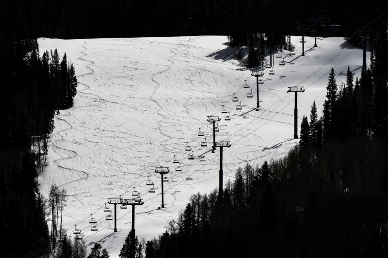 This Tuesday, March 24, 2020 photo shows ski lifts empty in Vail, Colo., after Vail Ski Resort closed for the season amid the COVID-19 pandemic. The closure has ended the normally busy spring ski season more than a month early. (AP Photo/Michael Ciaglo)