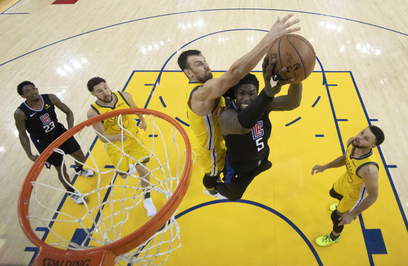 Los Angeles Clippers forward Montrezl Harrell (5) shoots under Golden State Warriors center Andrew Bogut during the second half of Game 2 of a first-round NBA basketball playoff series in Oakland, Calif., Monday, April 15, 2019. (Kyle Terada/Pool Photo via AP)