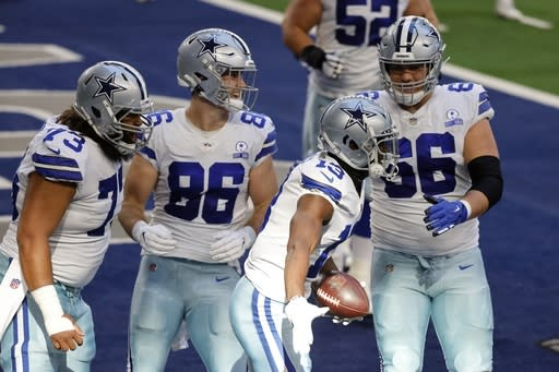 Dallas Cowboys' Joe Looney (73), Dalton Schultz (86), and Connor McGovern (66) celebrate with Michael Gallup (13) after his touchdown catch in the first half of an NFL football game against the San Francisco 49ers in Arlington, Texas, Sunday, Dec. 20, 2020. (AP Photo/Ron Jenkins)