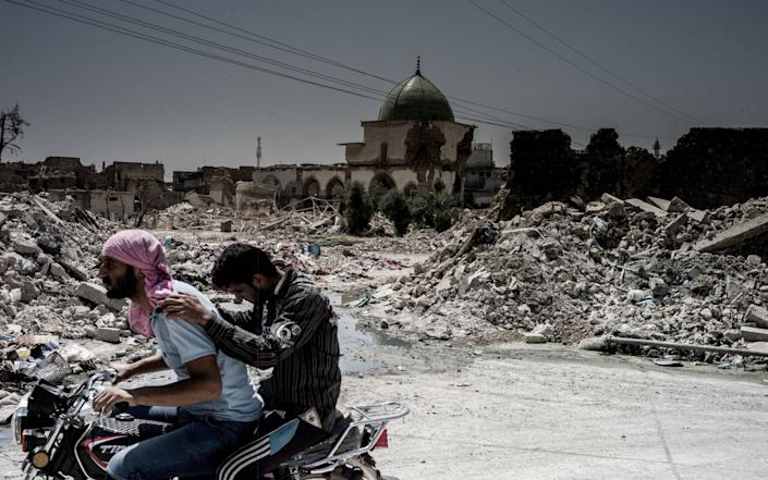 Two men pass the remnants of the Great Al Nuri mosque in the centre of the Old town of Mosul. The mosque was destroyed by IS in 2017 - Gus Palmer