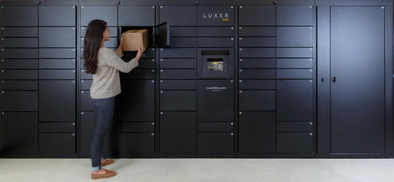 This photo provided by Luxer One shows a woman removing a package from one of Luxer's access lockers in San Francisco, Calif. Luxer One provides secure lockers in buildings in the United States and Canada that can be accessed by both delivery companies and residents. (Luxer One via AP)