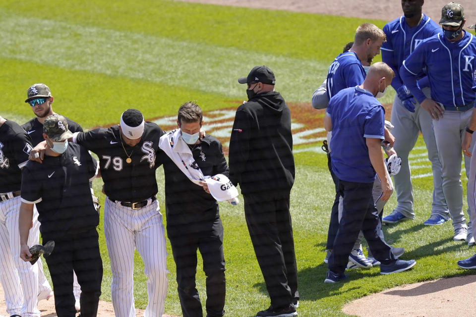 Chicago White Sox's Jose Abreu, left, heads to the dugout as Kansas City Royals' Hunter Dozier heads to his dugout after they collided along the first base line in the second inning of the first game of a baseball doubleheader Friday, May 14, 2021, in Chicago. (AP Photo/Charles Rex Arbogast)