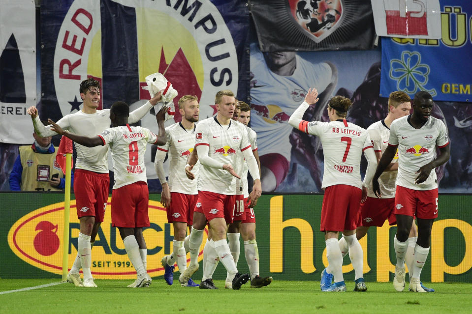 Leipzig's Patrik Schick, left, celebrates with his teammates after he scored his side's second goal during the German Bundesliga soccer match between Leipzig and Augsburg at the Red Bull Arena stadium in Leipzig, Germany, Saturday, Dec. 21, 2019. (AP Photo/Jens Meyer)