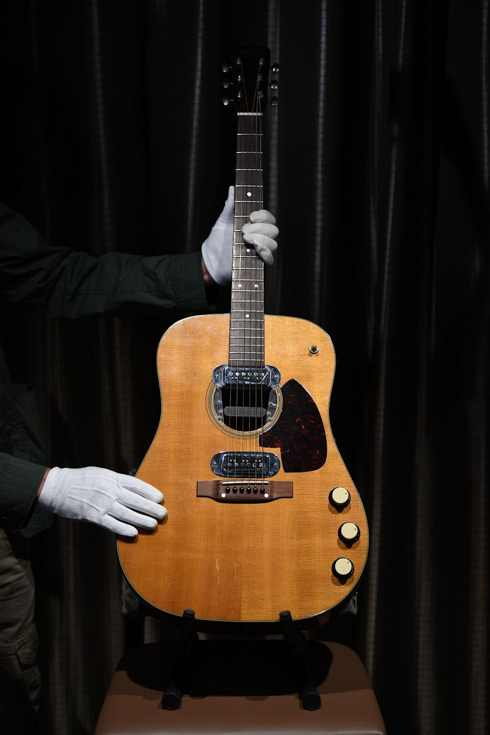 Co-owner of Julien's Auctions, Martin Nolan displays the guitar used by musician Kurt Cobain during Nirvana's famous MTV Unplugged in New York concert in 1993, at the Hard Rock Cafe Piccadilly Circus in central London on May 15, 2020, prior to the auction of the guitar in Beverly Hills in June. - The 1959 Martin D-18E featured in the band's performance in November 1993, five months before Cobain's death at the age of 27. (Photo by DANIEL LEAL-OLIVAS / AFP) (Photo by DANIEL LEAL-OLIVAS/AFP via Getty Images)