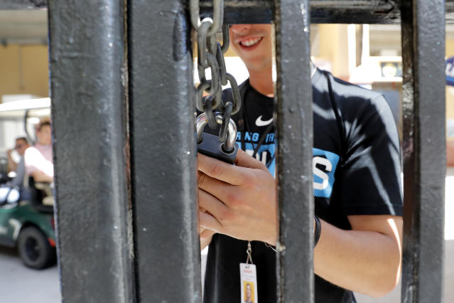 An employee of Roger Dean Stadium locks a gate, Friday, March 13, 2020, in Jupiter, Fla. Major League Baseball has delayed the start of its season by at least two weeks because of the coronavirus outbreak as well as suspended the rest of its spring training game schedule. (AP Photo/Julio Cortez)