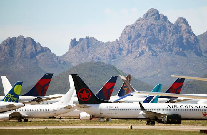 Three Delta Air Lines passenger jets are parked among other airliners at the Pinal Airpark on Tuesday, March 17, 2020, in Marana, Ariz. Because of the coronavirus outbreak, Delta wide-body aircraft are being moved to storage in Arizona.