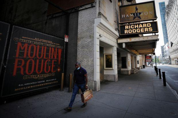 A man walks by Broadway theaters closed due to Covid-19