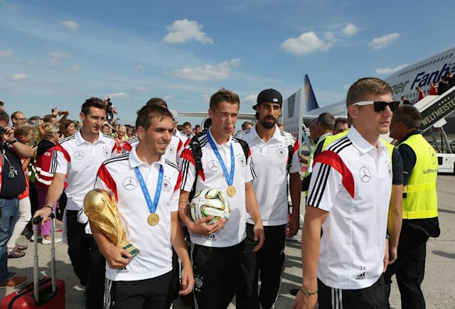 German national soccer players from left : Miroslav Klose, Philipp Lahm, Lars Bender, Sami Khedira and Toni Kroos arrive with the team at Tegel airport in Berlin Tuesday July 15, 2014. Germany beat Argentina 1-0 on Sunday to win its fourth World Cup title. (AP Photo/Karina Hessland,pool)