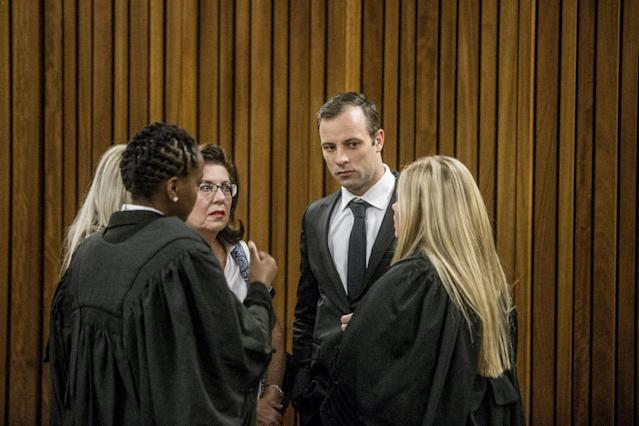 Oscar Pistorius speaks to members of his legal team before appearing for a postponement of his sentencing hearing at the High Court in Pretoria, South Africa, April 18, 2016. REUTERS/Marco Longari/Pool