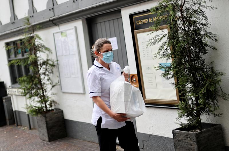 A woman wearing a face mask walks outside the Crown and Anchor pub following a spike in cases of the coronavirus disease (COVID-19) to visitors of the pub in Stone, Britain, July 29, 2020. REUTERS/Carl Recine