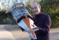 Model enthusiast of Gerry Anderson's creations, David Sisson, holds an original Battlehawk model from Gerry Anderson and Christopher Burr's Terrahawks, at Ewbank's Auctioneers in Woking