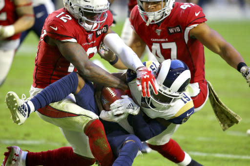 Los Angeles Rams wide receiver JoJo Natson (19) is hit by Arizona Cardinals wide receiver Pharoh Cooper (12) on a punt return during the second half of an NFL football game, Sunday, Dec. 1, 2019, in Glendale, Ariz. (AP Photo/Ross D. Franklin)