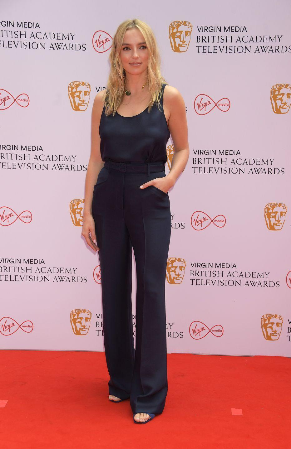 <p>Jodie Comer kept it pared-back and elegant in a navy silk tank and matching tailored trousers by Gabriela Hearst.</p>