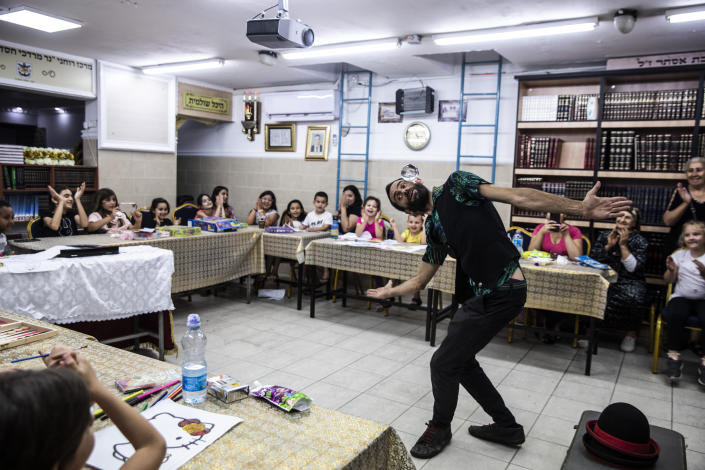 Israeli juggler Guy Kaplan performs for children in a bomb shelter, following rocket attacks fired from the Gaza Strip, in Ashdod, Israel, Thursday, May 20, 2021. (AP Photo/Heidi Levine)