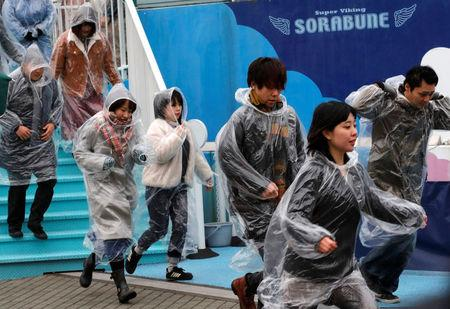 Participants run during an anti-missile evacuation drill at the Tokyo Dome City amusement park in Tokyo
