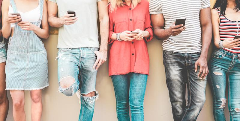Group of millennial friends watching smart mobile phones - Teenagers addiction to new technology trends - Concept of youth, tech, social and friendship - Focus on smartphones