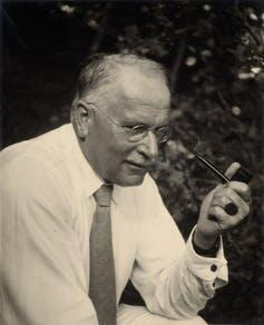 Black and white photo of older man wearing a tie and holding a pipe.