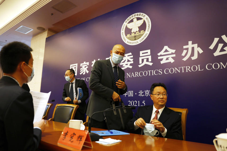 Deng Ming, deputy director of China's National Narcotics Control Commission, center leaves after attending a press conference in Beijing on Tuesday, May 11, 2021. China on Tuesday said it will add all synthetic cannabinoids to its list of banned drugs, in what it described as a first in the world, to curb their manufacturing, trafficking and abuse. (AP Photo/Ng Han Guan)