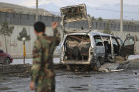 Security personnel inspect the site of a deadly bomb attack in Kabul, Afghanistan, Sunday, March 7, 2021. The bomb attached to minibus exploded Sunday in the capital, Kabul, killing and wounding several people. (AP Photo/Rahmat Gul)