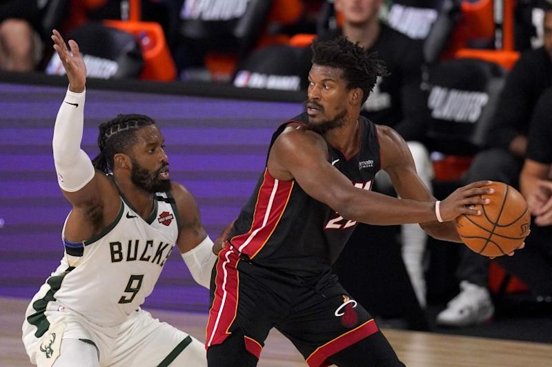 Milwaukee Bucks' Wesley Matthews (9) defends as Miami Heat's Jimmy Butler (22) handles the ball during the second half of an NBA basketball conference semifinal playoff game, Monday, Aug. 31, 2020, in Lake Buena Vista, Fla. (AP Photo/Mark J. Terrill)
