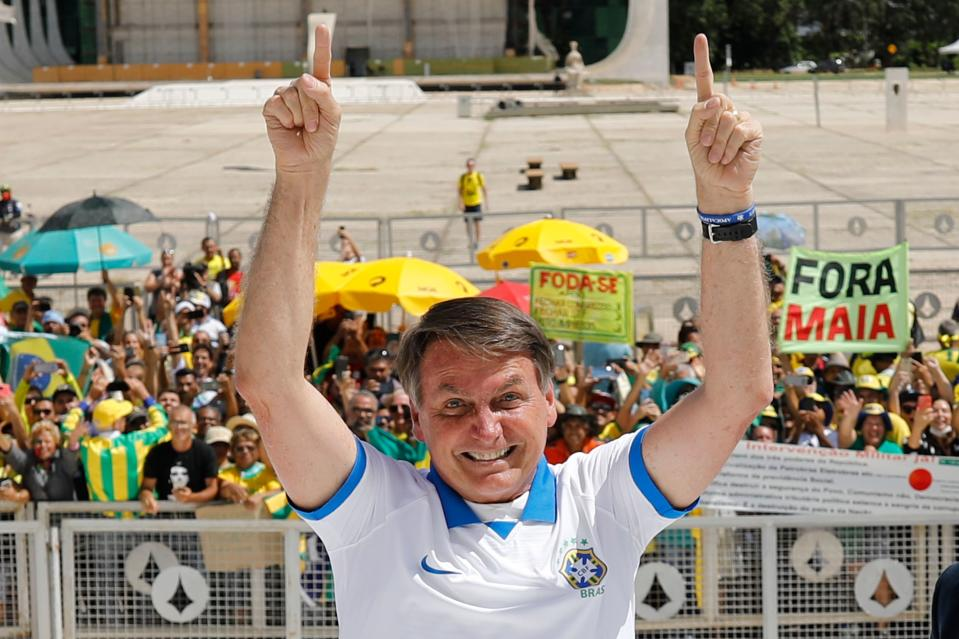 TOPSHOT - Brazilian President Jair Bolsonaro greets supporters in front of the Planalto Palace, after a protest against the National Congress and the Supreme Court, in Brasilia, on March 15, 2020. (Photo by Sergio LIMA / AFP) (Photo by SERGIO LIMA/AFP via Getty Images)