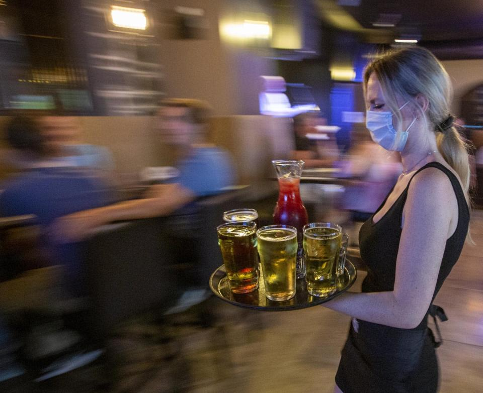 """<span class=""""caption"""">A waitress wears a mask while carrying drinks for guests inside the Blu Martini restaurant in Kingston, Ont., in July 2021. </span> <span class=""""attribution""""><span class=""""source"""">THE CANADIAN PRESS/Lars Hagberg </span></span>"""
