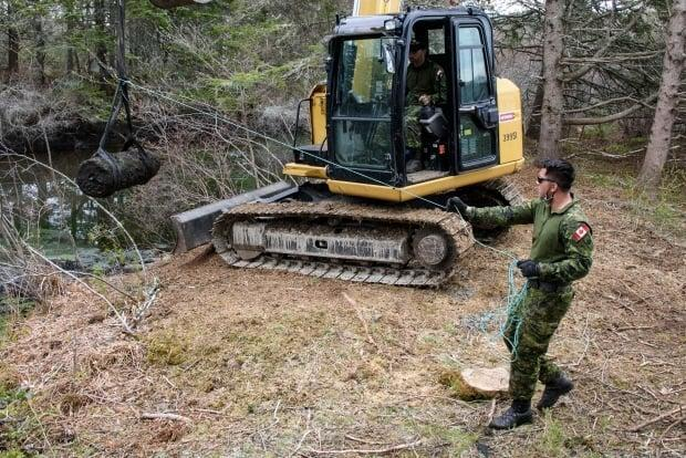 Petty Officer 2nd Class Tom Amos guides the bomb with a rope as Petty Officer 1st Class Barry Noseworthy uses an excavator to remove it from a pond.