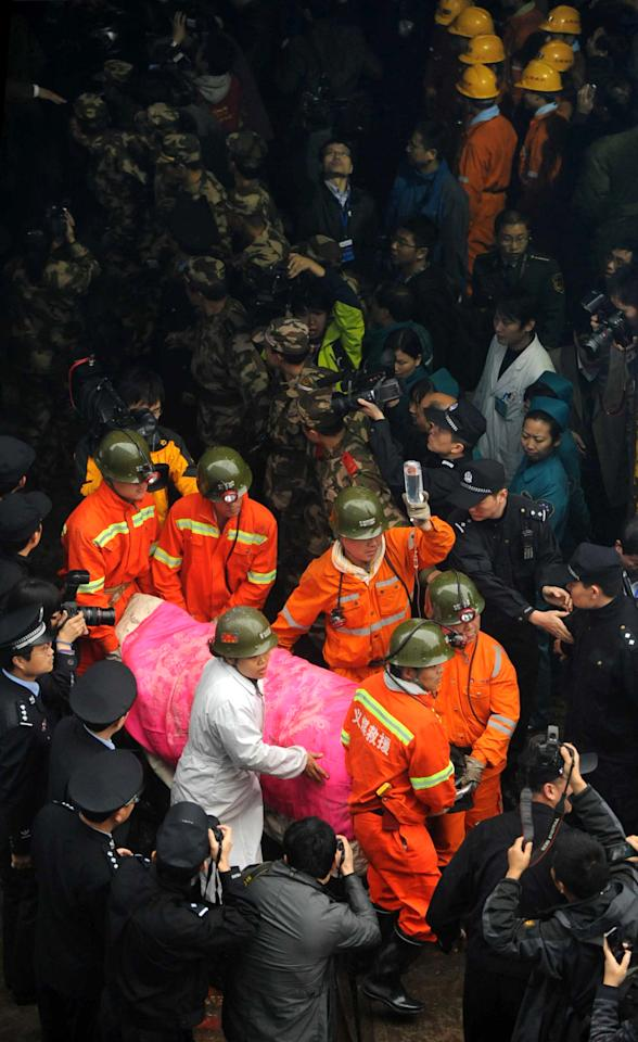 In this photo released by China's Xinhua News Agency, a miner is carried out of the shaft of the Qianqiu Coal Mine in Sanmenxia City, central China's Henan Province, Saturday, Nov. 5, 2011. Forty-five grimy, exhausted miners trapped by a cave-in were rescued Saturday, ending a 36-hour ordeal in the world's most dangerous country for the industry. (AP Photo/Xinhua, Zhu Xiang) NO SALES
