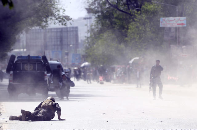 <p>A security force and a civilian lie low at the site of a suicide attack after the second bombing in Kabul, Afghanistan, April 30, 2018. (Photo: Massoud Hossaini/AP) </p>