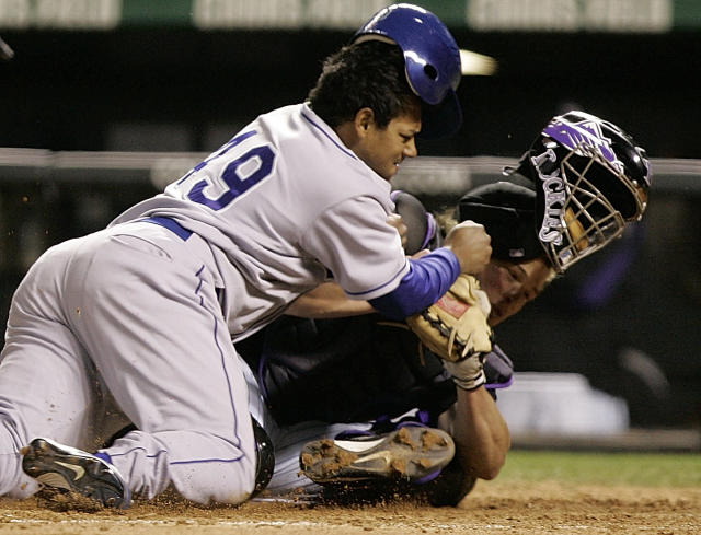 FILE - In this Sept. 27, 2006, file photo, Los Angeles Dodgers' Delwyn Young, left, is out at home plate as he collides with Colorado Rockies catcher JD Closser during the seventh inning of a baseball game in Denver. New York Mets general manager Sandy Alderson, chairman of the rules committee, announced Wednesday, Dec. 11, 2013, that Major League Baseball plans to eliminate home plate collisions. He said player health and increased awareness of concussions were behind the decision.(AP Photo/Jack Dempsey, File)