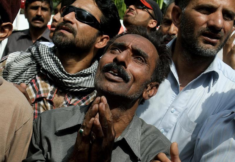Pakistanis pray for people stranded in a building that caught on fire, not pictured, in Lahore, Pakistan, Thursday, May 9, 2013. The 13-storey government building caught fire and quickly intensified spreading to three floors of the tall building. (AP Photo/K.M. Chaudary)