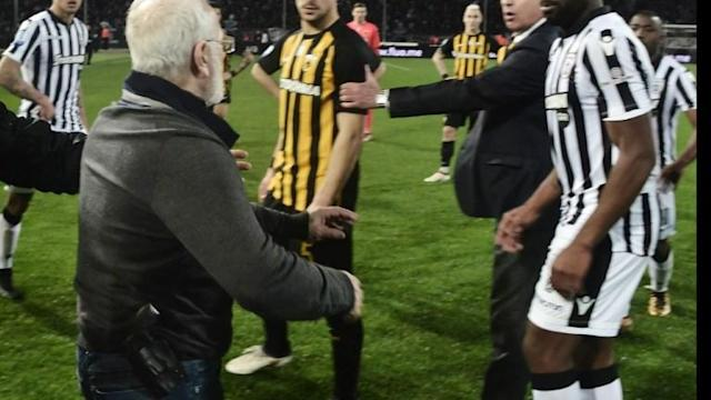 Football fans react after Greece's top-flight football championship is suspended indefinitely, hours after the owner of the PAOK team invades the pitch with a gun strapped to his belt.
