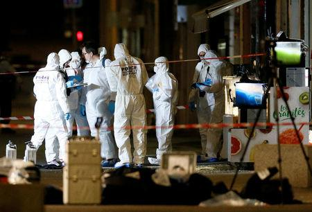 Forensic officers inspect the site of a suspected bomb attack in central Lyon