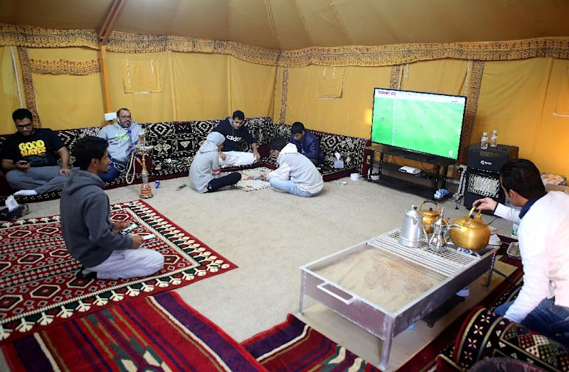 Men watch TV play games and drink tea while gathering at a tent in a & Kuwaitis seek roots in upmarket tents under the stars