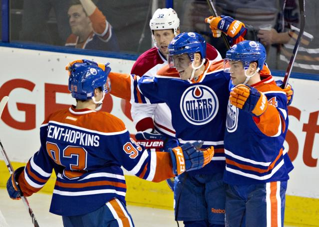 Montreal Canadians' Travis Moen (32) skates past as Edmonton Oilers' Ryan Nugent-Hopkins (93), David Perron (57) and Taylor Hall (4) celebrate a goal during second-period NHL hockey game action in Edmonton, Alberta, Thursday, Oct. 10, 2013. (AP {Photo/The Canadian Press, Jason Franson)