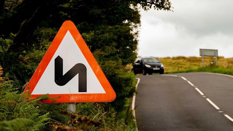 Double bend warning road sign on UK country road with car approaching