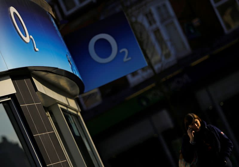 A woman speaks on her mobile telephone outside an O2 shop in Loughborough