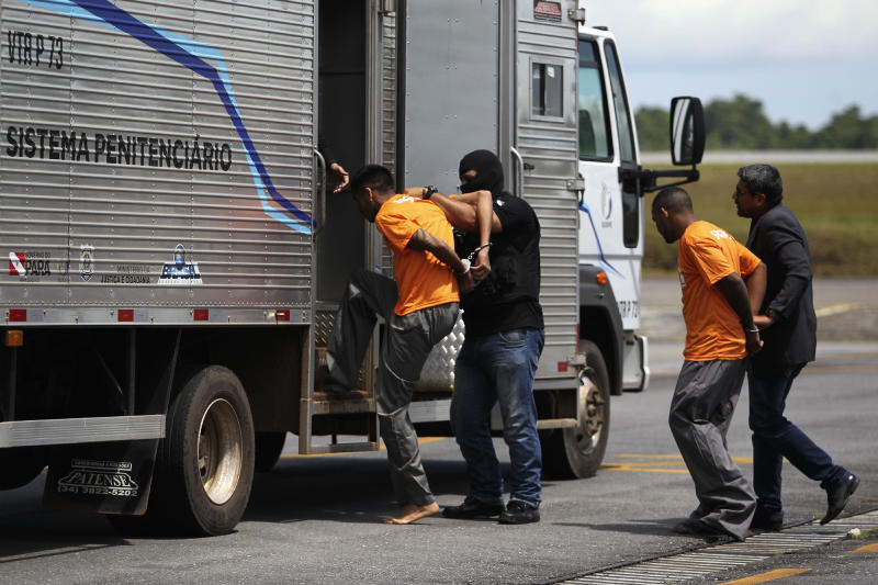 Prisoners allegedly involved in the killing of other inmates during a prison riot in Altamira, are led to a prisoner transport vehicle to be driven to another penitentiary, after arriving at the airport in Belem, Brazil, Tuesday, July 30, 2019. Dozens of relatives of inmates killed during in the riot in northern Brazil gathered at a coroner's office Tuesday to identify the 57 victims. (AP Photo/Raimundo Pacco)