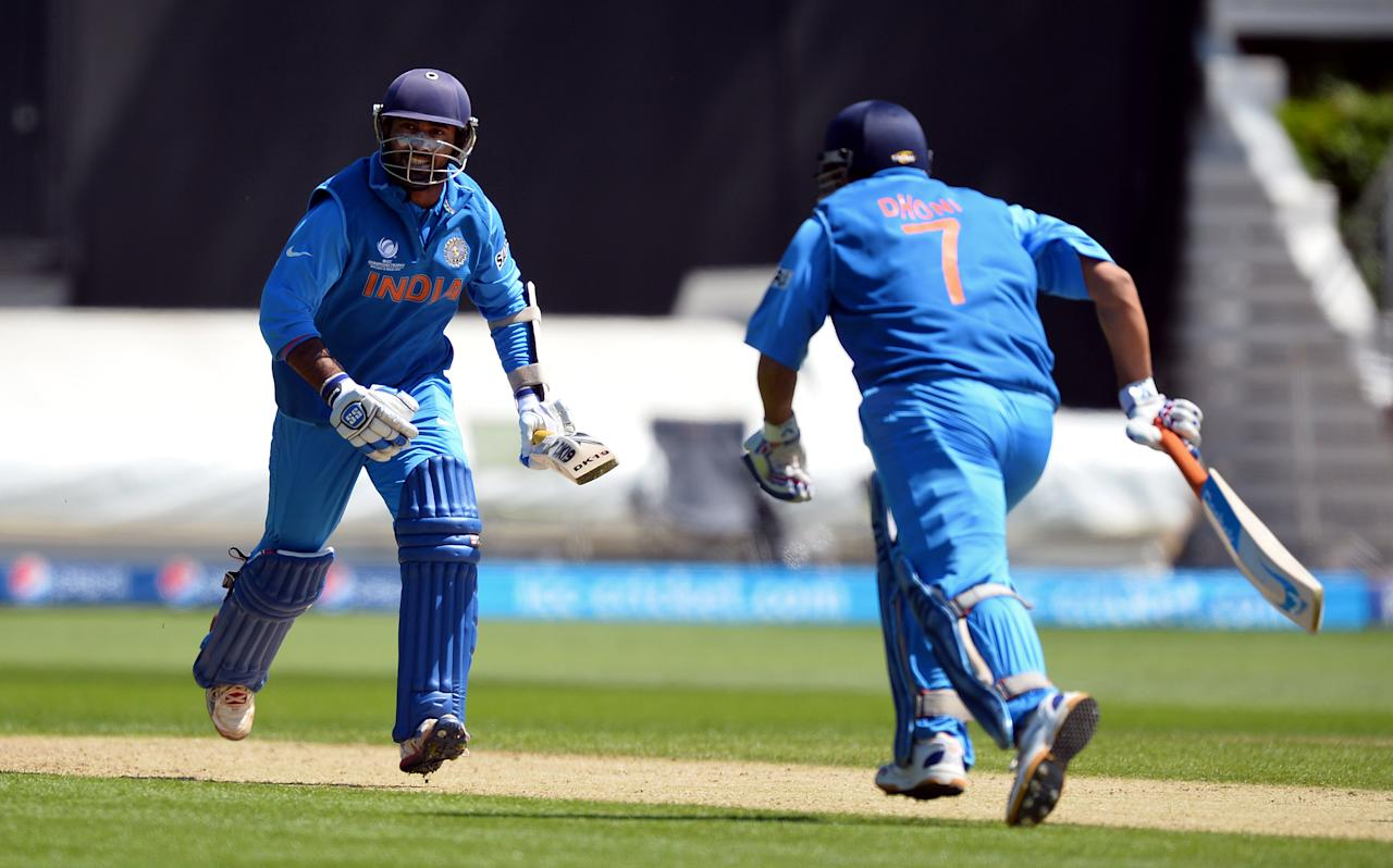 India's captain Mahendra Singh Dhoni (R) and teammate Dinesh Karthik run between the wickets during the warm-up cricket match ahead of the 2013 ICC Champions Trophy between India and Australia at The Cardiff Wales Stadium in Cardiff, Wales on June 4, 2013.  India won the toss and elected to bat first.  AFP PHOTO/Paul Ellis        (Photo credit should read PAUL ELLIS/AFP/Getty Images)
