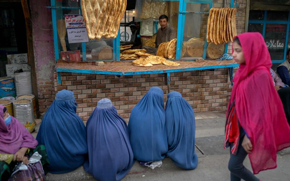 Burqa-clad women wait for free bread in front of a bakery in Kabul - BULENT KILIC /AFP