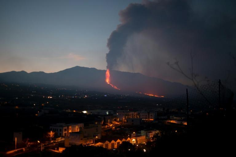 Despite the Cumbre Vieja volcano spewing lava, ash and smoke as here in Los Llanos de Aridane on La Palma, life is continuing almost as normal in much of the island (AFP/JORGE GUERRERO)
