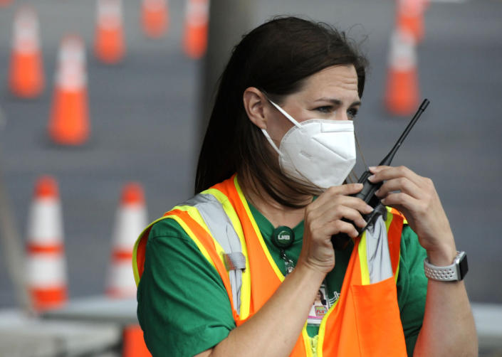 Cathy Fuller, a nurse at the University of Alabama at Birmingham, talks into a handheld radio on Tuesday, May 18, 2021, at a mass COVID-19 immunization site in Hoover, Ala., where declining demand prompted a shutdown. While initially capable of vaccinating as many as 2,400 people daily, site workers said far fewer people have been showing up for shots even though only about 25% of Alabama's population is fully vaccinated. (AP Photo/Jay Reeves)
