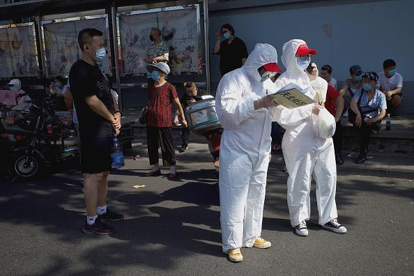 Medical staff members in full protective gear stand outside the Guangan sports centre to assist people who live near or who have visited the Xinfadi Market, a wholesale food market where a new COVID-19 coronavirus cluster has emerged, for testing in Beijing.