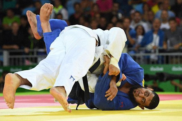 Israel's Or Sasson (white) competes with Egypt's Islam El Shehaby during their men's +100kg judo contest match on August 12, 2016 (AFP Photo/Toshifumi Kitamura)
