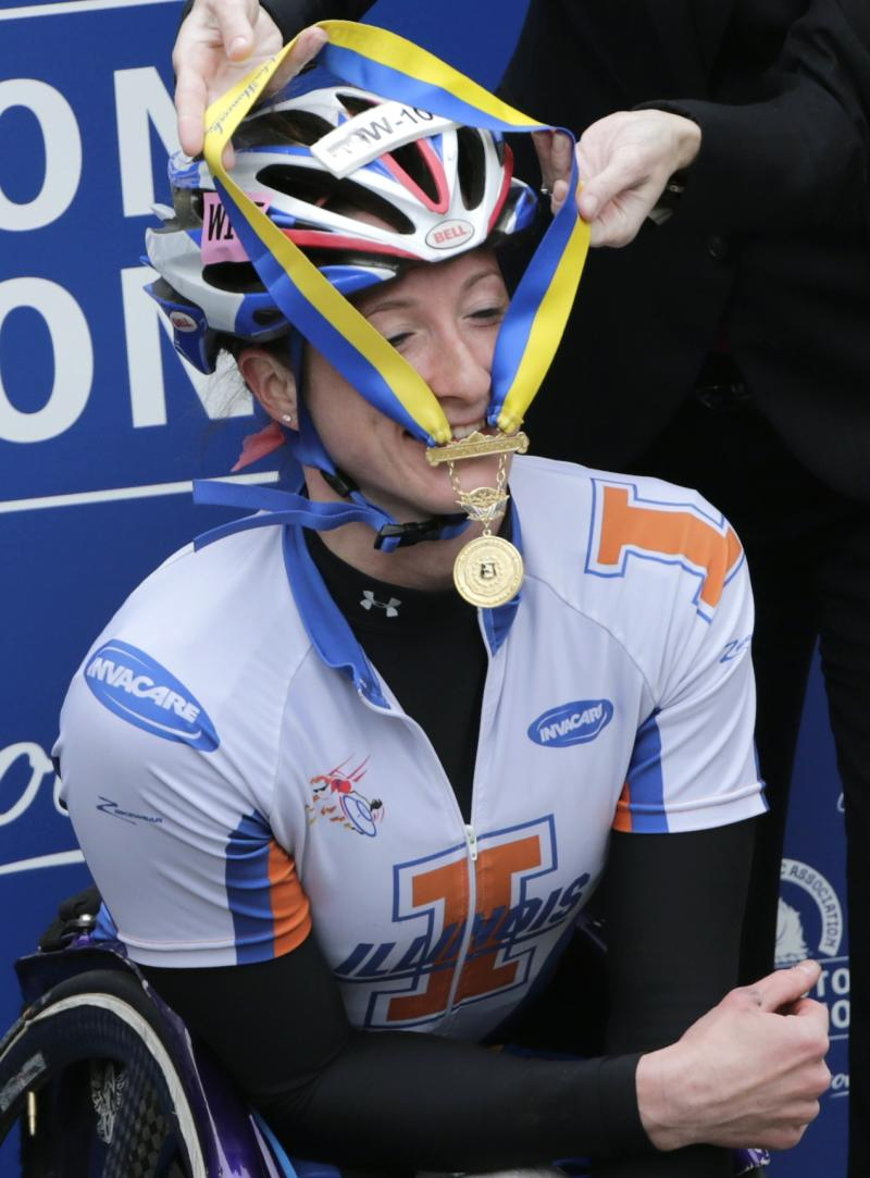 """FILE - In this April 15, 2013 file photo, Tatyana McFadden, of the United States, smiles as her winner's medal gets stuck on her helmet after winning the women's wheelchair division of the 2013 Boston Marathon in Boston. EBay says it is monitoring listings to ensure nobody uses the auction website to profit from the Boston Marathon bombings. Jonathan Resnick's medal is for sale on the site and proceeds will go directly to charity. He said he read on a runners' discussion board that medals were being sold and realized """"it was the least I could do to make something good from something bad.""""  (AP Photo/Charles Krupa, File)"""