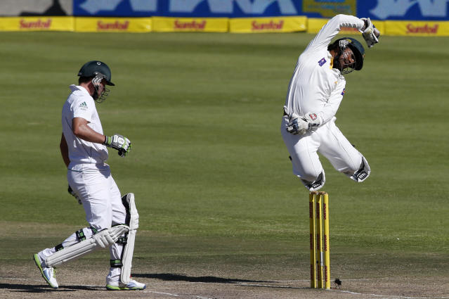 Pakistan's Sarfraz Ahmed jumps for the ball as South Africa's AB de Villiers (L) makes his ground on the fourth day of the second cricket test match in Cape Town, February 17, 2013. REUTERS/Mike Hutchings (SOUTH AFRICA - Tags: SPORT CRICKET TPX IMAGES OF THE DAY) - RTR3DX63