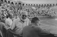 """<p>Hemingway was an avid spectator of Spanish bullfights. Here, he attends an event in 1960. His obsession can be <a href=""""https://www.historytoday.com/archive/natural-histories/whom-bull-tolls"""" rel=""""nofollow noopener"""" target=""""_blank"""" data-ylk=""""slk:seen throughout his works"""" class=""""link rapid-noclick-resp"""">seen throughout his works</a>.</p>"""