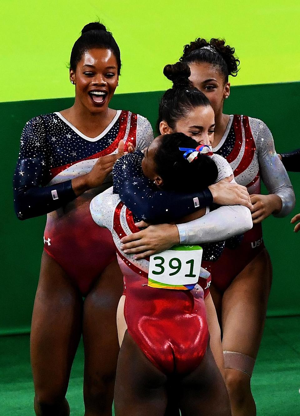 <p>Simone Biles (front) of the United States is congratulated by her team mates on the floor during the Artistic Gymnastics Women's Team Final on Day 4 of the Rio 2016 Olympic Games at the Rio Olympic Arena on August 9, 2016 in Rio de Janeiro, Brazil. (Photo by Quinn Rooney/Getty Images) </p>